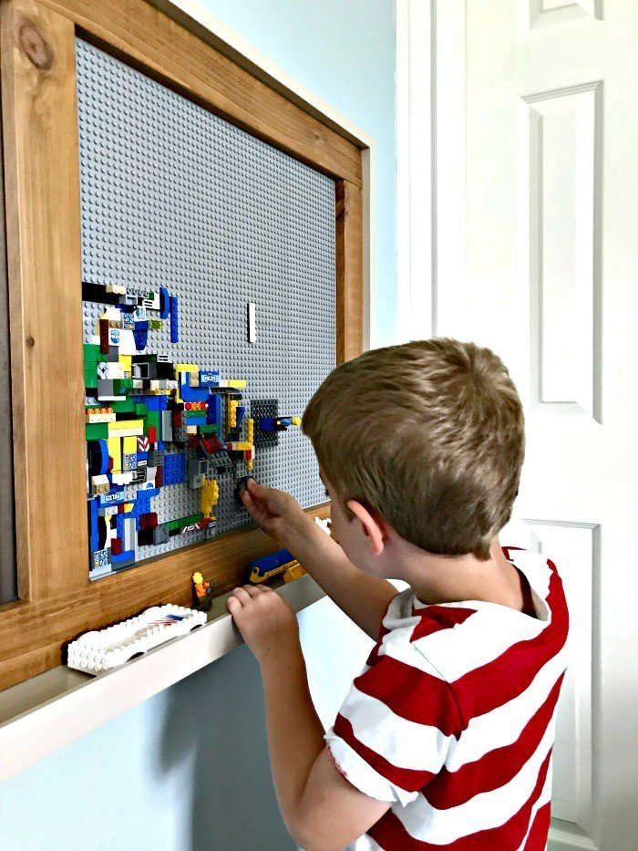 A kid playing at a grey framed lego board. Build a fun DIY Modern Farmhouse Kids Activity Wall Board. With 20 Ideas for board options that work for kids, teens, and adults. #ModernFarmhouse #KidsFurniture #DIYKids #AbbottsAtHome