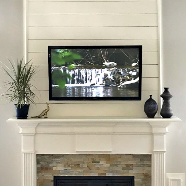 Shiplap above a white traditional fireplace mantel.
