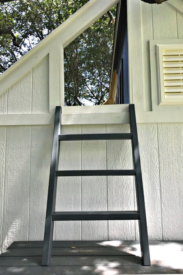 A small DIY step ladder leading to a treehouse
