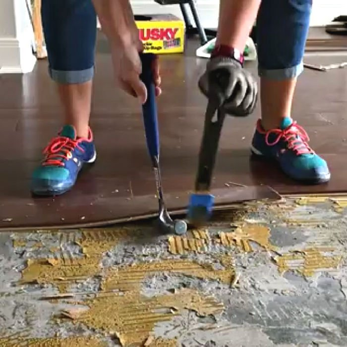How to use a pry bar and hammer to remove glued engineered flooring on concrete.