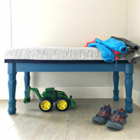 I LOVE this easy DIY Upholstered Entryway Bench Build Plan made with cheap turned legs. It's a beautiful bench you can paint or stain. Steps to build with a hard top or upholstered top.