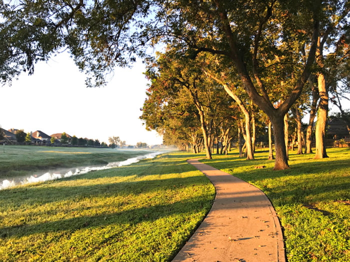 Walking trail with a sidewalk, trees, water, and grass.